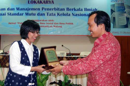 After delivering her material, Myrtati Dyah Artaria receives a souvenir from the Dean of Faculty of
