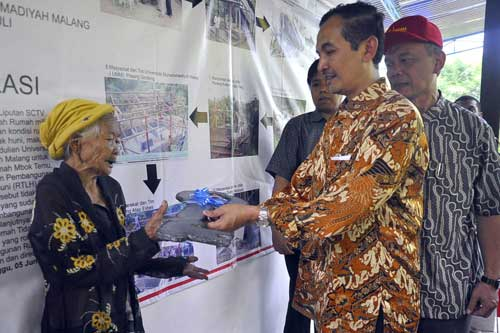Mbah Kunthi received a symbolic key from Vice Rector II of UMM, Drs. Mursidi, M,M that was accompanied